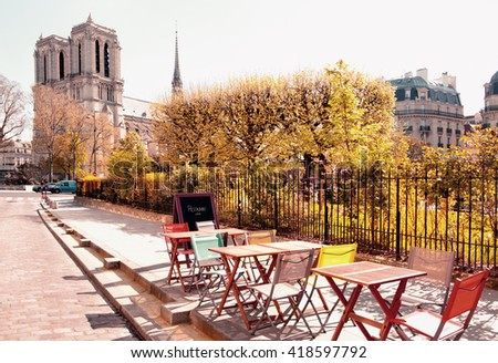 Autumn in Paris, tables and chairs of an outddoor cafe next to Notre Dame Cathedral. This image is toned. - stock photo