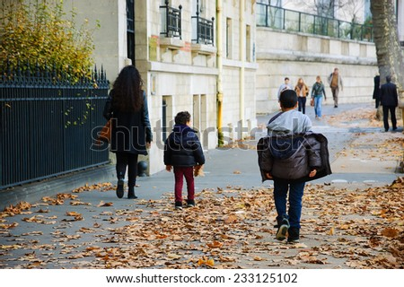 Autumn in Paris. Woman and two kids (mother and sons) walking over the faded plane-tree leaves covered pavement on typical Parisian street. - stock photo