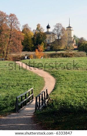 Autumn in village. A footpath, the bridge, church. - stock photo