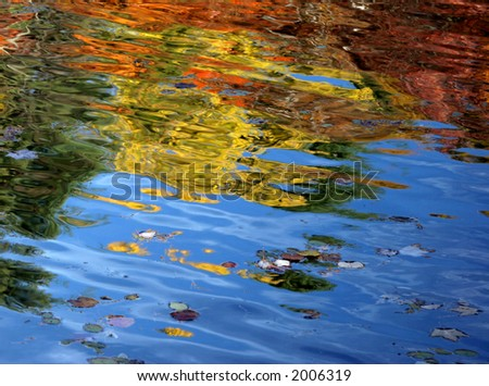 Autumn lake reflection with waves - stock photo
