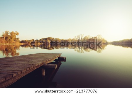 Autumn lake with wooden dock  - stock photo