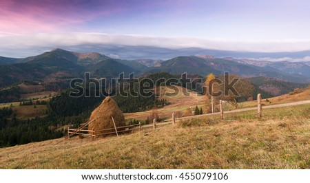 Autumn landscape at sunset. Haystack on the meadow in a mountain village. Sky with beautiful clouds. Carpathians, Ukraine, Europe - stock photo
