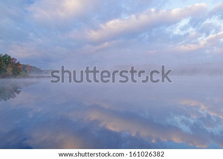 Autumn landscape at twilight with reflections in calm water, Deep Lake, Yankee Springs State Park, Michigan, USA  - stock photo