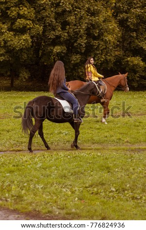 Autumn landscape, beautiful brunette girls with long hair posing with a red and brown horses in the forest