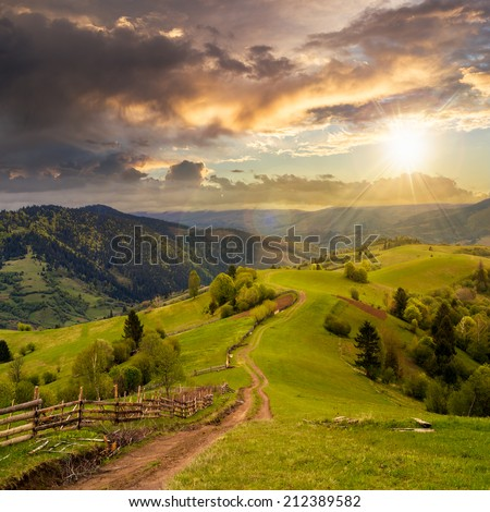 autumn landscape. fence near the meadow path on the hillside. forest in fog on the mountain. - stock photo