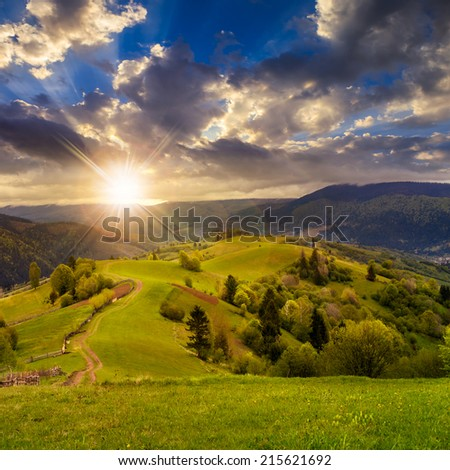 autumn landscape. fence near the meadow path on the hillside. forest in fog on the mountain in rays of sunset