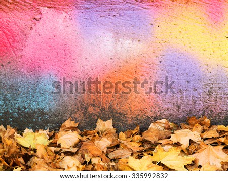 Autumn Landscape, focus on the fallen leaves on the bright background of the concrete wall, weathered with cracks and scratches. Grungy concrete surface. Great background for each of your project. - stock photo