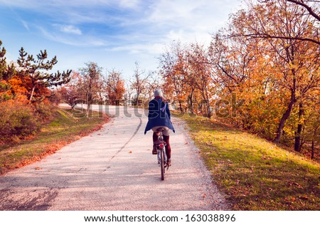 Autumn landscape. Girl cycling up to the mountain. - stock photo