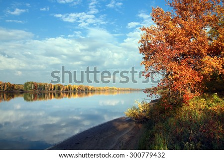 autumn landscape of colorful trees reflected in the mirrored surface of the calm river - stock photo