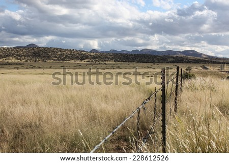Autumn landscape of fenced semi-desert grasslands and hills on cloudy afternoon/Dry  Pasture Grasslands with Hills in Cloudy Autumn Landscape/Fenced dry grassy pasture with hills and clouds - stock photo