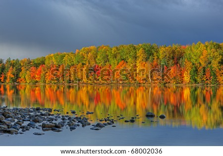 Autumn landscape of Moccasin Lake with reflections of trees in calm water and storm clouds, Michigan's Upper Peninsula, USA - stock photo