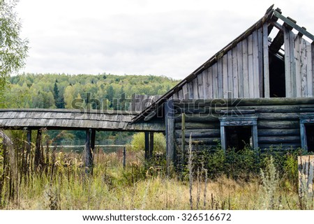 Autumn landscape. Old abandoned village on the empty field. Deteriorated typical ancient wooden abandoned house at village. Destroyed abandoned house standing in the forest.  - stock photo