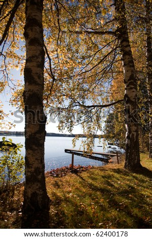 Autumn landscape with colorful trees by the lake - stock photo