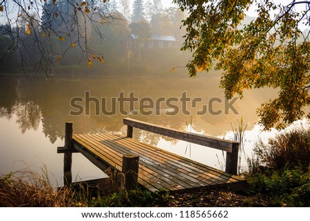 Autumn landscape with mist on the lake and a pier bathing on sunshine - stock photo