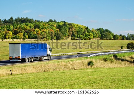 Autumn landscape with road and truck, in the foreground meadow, forest in the background - stock photo