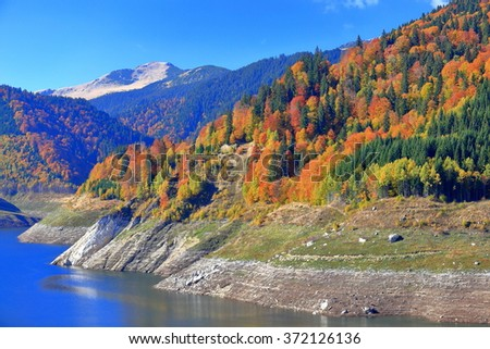 Autumn landscape with sunny forest on the mountains above glacier lake - stock photo