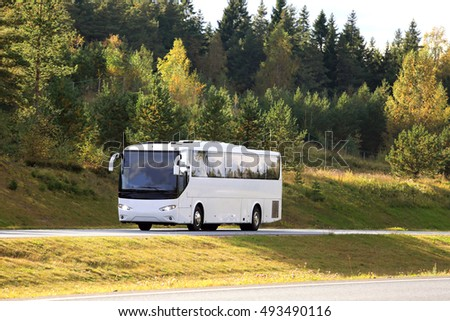 Autumn landscape with white coach bus traveling on motorway. Copy space for your text.