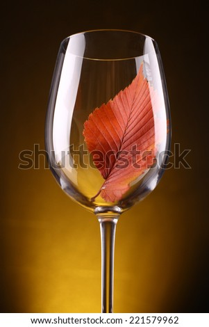 Autumn leaf in a tall wine glass over a warm dark background - stock photo