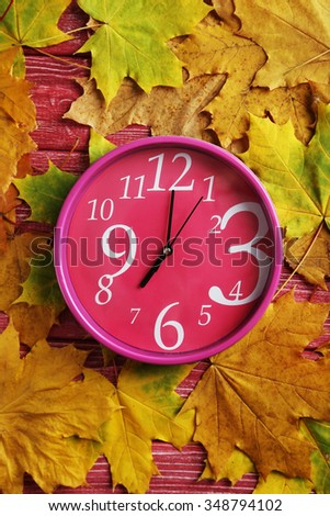 Autumn leaf with o'clock on a red wooden table - stock photo