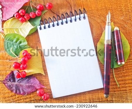 autumn leaves and notepad on wooden background - stock photo