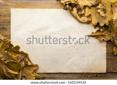 autumn leaves and old paper on wooden background