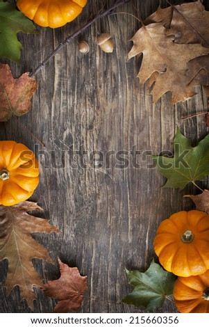 Autumn leaves and pumpkins on the wooden background - stock photo