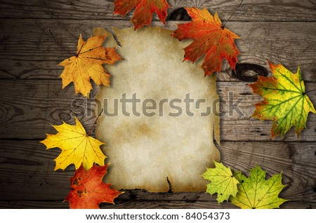 Autumn leaves over old wooden background with blank paper scroll - stock photo