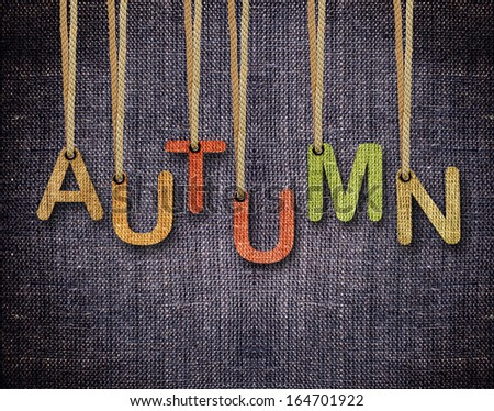 Autumn letters hanging strings with blue sackcloth background. - stock photo