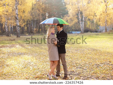 Autumn, love, relationships and people concept - lovely young couple with colorful umbrella walking in the park - stock photo