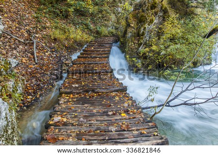 Autumn majestic view on turquoise water and falls with wooden path road in the Plitvice Lakes National Park. Croatia. - stock photo