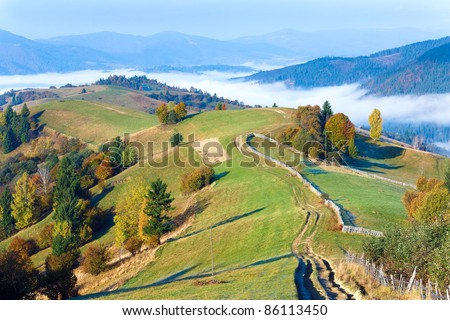 Autumn misty morning  mountain view and country dirty road (Mighgirya village outskirts, Carpathian Mt's, Ukraine). - stock photo