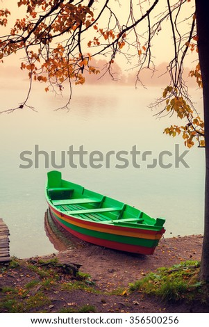 Autumn misty morning. Wooden boat on the river bank. - stock photo