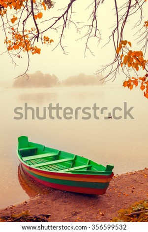 Autumn misty morning. Wooden boat on the river bank - stock photo