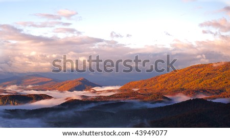 Autumn morning mountain view with fog nestled in the mountain valleys.