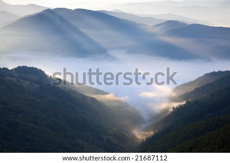Autumn morning mountain view with sunbeam and haze - stock photo