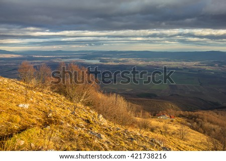 Autumn mountain hill and a distant hut  - stock photo