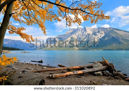 Autumn mountain landscape with blue lake and vibrant overhanging fall leaves - stock photo