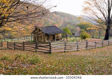 Autumn Mountains with Log Cabin. wooden outhouse and split rail fence.