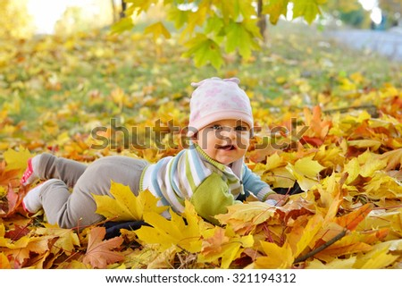 Autumn newborn baby girl lying in maple leaves and looks at camera. Close up portrait. - stock photo