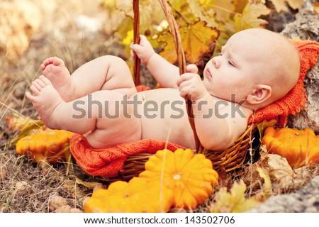 Autumn newborn baby sleeping in basket. Close up portrait. - stock photo