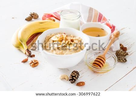 Autumn oatmeal in white bowl banana honey yogurt white wood background - stock photo