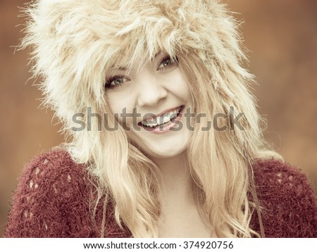 Autumn or winter fashion. Closeup happy young woman wearing fashionable wintertime clothes fur cap outdoor portrait