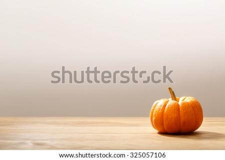 Autumn orange small pumpkin on wooden table - stock photo