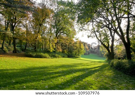 Autumn Park at sunset. The shadows on the green grass lawn. Autumn landscape. - stock photo