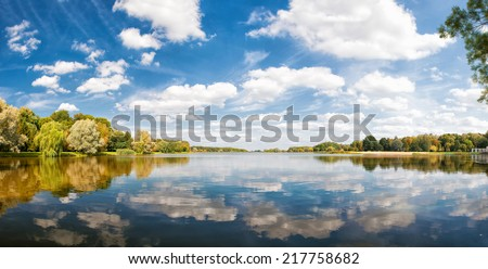 autumn park, trees and blue sky reflected in water, sunny day - stock photo