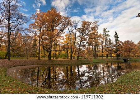 Autumn park with golden and red maple leaves and the pond