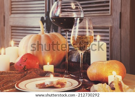 Autumn place setting. Thanksgiving dinner. Fall season fruit, pumpkins, plates, wine and candles. Thanksgiving dinner - stock photo