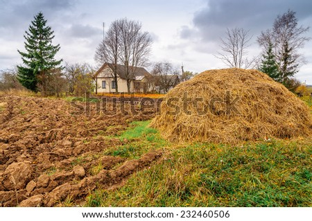 Autumn plowed field with trees, house and haystack  - stock photo