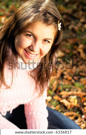 Autumn Portrait - Beautiful young girl in the park with golden light