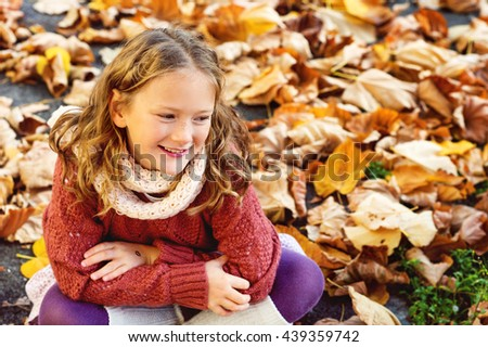Autumn portrait of a cute little girl with curly hair, having fun outdoors on a nice sunny day - stock photo